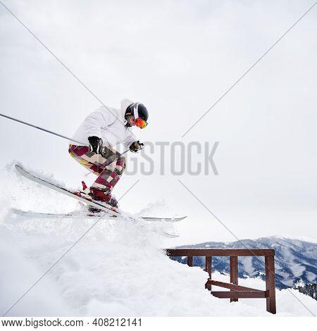 Side View Of Young Man Skier In White Winter Jacket Sliding Down Snow-covered Slope On Skis With Fix