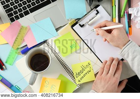 Man Writing At Messy Table, Top View. Concept Of Being Overwhelmed By Work