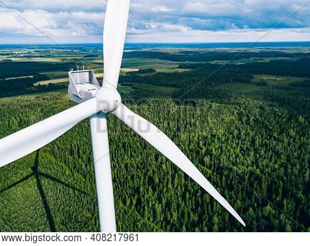 Aerial View Of Windmills In Green Summer Forest In Finland Close Up. Wind Turbines For Electric Powe