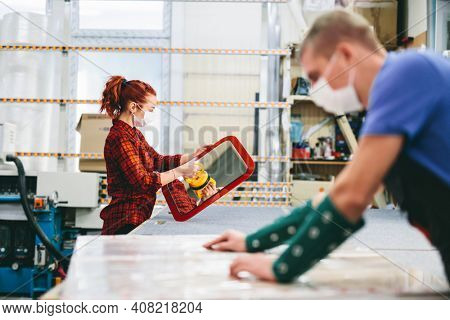 Man and woman in face masks working on glass pane in glazier workshop. Industry and work during coronavirus Covid-19