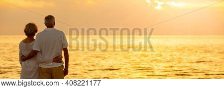 Panorama senior man and woman couple embracing at sunset or sunrise on a deserted tropical beach panoramic web banner