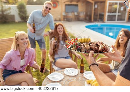 Group Of Cheerful Young Friends Gathered Around The Table, Drinking Beer And Having Fun At Backyard