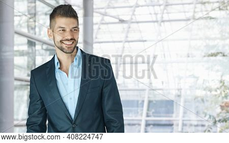 Happy dedicated young businessman in jacket looking away in office lobby. Man in business.