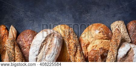 Banner With Different Types Of Bread On Dark Surface. Close Up. Bakery Concept. Empty Space For Text