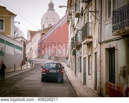 Lisbon, Portugal - Feb 9, 2018: Card Driving On Tiny Street Between Buildings With Church Of Santa E