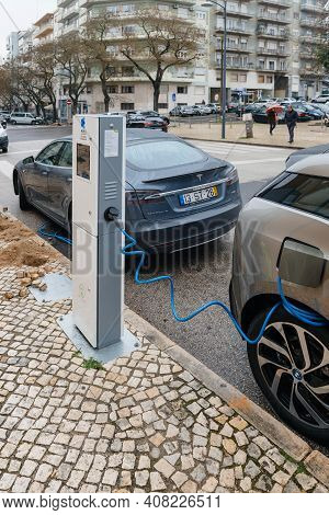 Lisbon, Portugal - Feb 9, 2018: Two Electric Cars Being Charged At Power Station One Tesla And One B