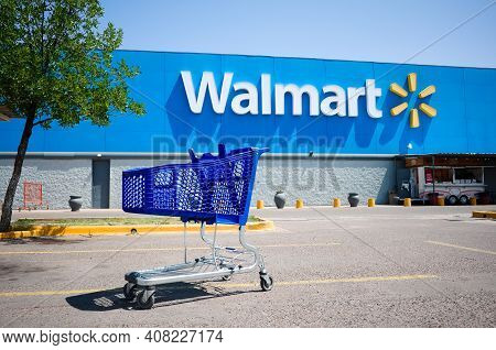 Mendoza, Argentina - January, 2020: Shopping Cart On A Parking Lot In Front Of Main Entrance To Walm