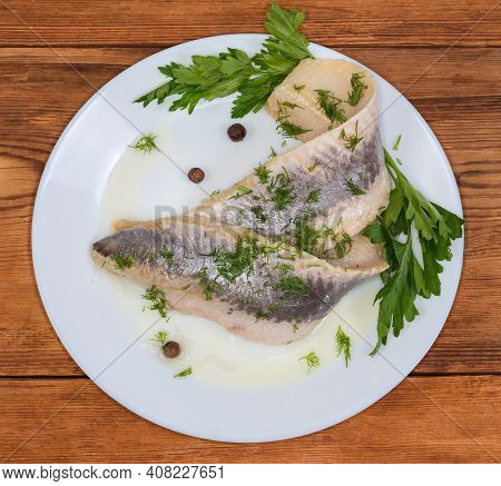 Pickled Mild Salted Herring Fillets Without Skin Sprinkled With Chopped Dill On A White Dish With Tw