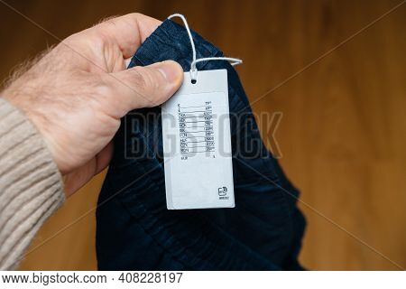 Pov Male Hand Holding New Pair Of Pants With Price Tag In Multiple International Currencies And Rfid