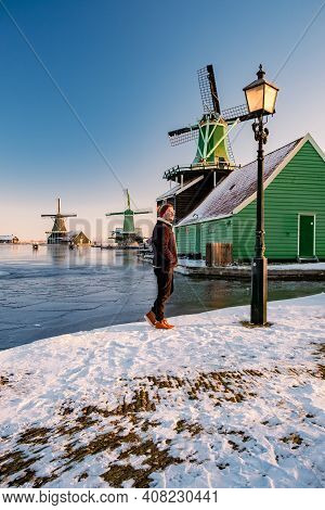 Young Man Walked In The Snow, Snow Covered Windmill Village In The Zaanse Schans Netherlands, Histor