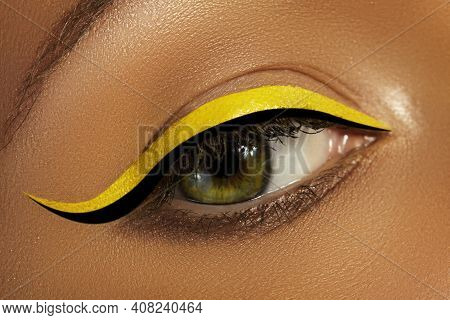 Close-up Female Eye With Bright Yellow Eyeliner Makeup. Neon Disco Make-up With Black Liner. Summer