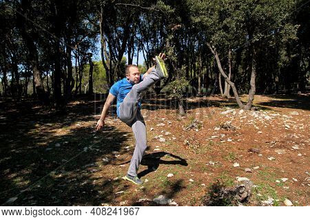 Muscular Man Doing Workout Is Warming Up By Rising Leg Up In The Air Exercise In Forest. Handsome Sp