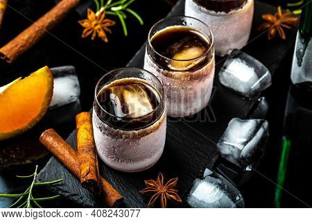 Frozen Herb Liqueur In Small Glass. Shot Glass Of Herb Liqueur With Cinnamon And Oranges On A Dark B