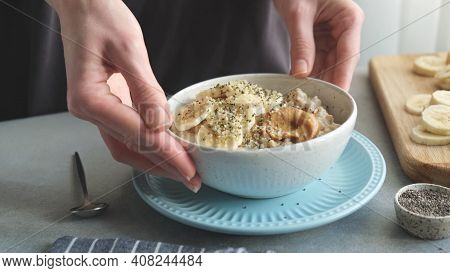 Female Hands Holding Bowl Of Vegan Oatmeal Porridge With Banana, Chia Seeds And Peanut Butter