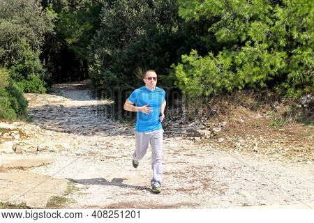 Running Muscular Man Athlete Runner Training Outdoor In Forest. Running Runner Sportsmen Wearing Spo