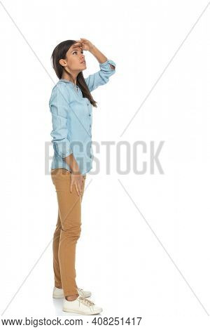 side view of a beautiful casual woman protecting her eyes from the sunlight in order to see better