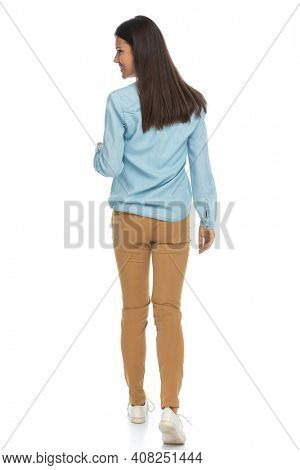 rear view of a beautiful casual woman walking ahead and looking aside against white background