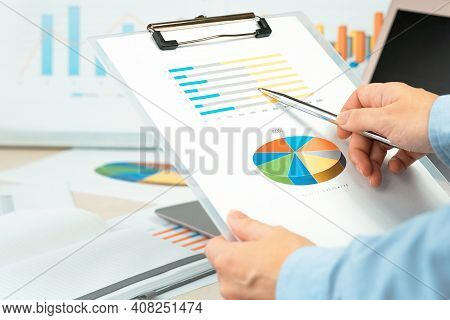 Finance And Business Concept. Hand Pointing At Statistics Chart. Calculator On Financial Graphs On D