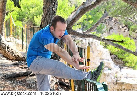 Handsome Young Man Is Doing Stretching Exercises In Forest. Sportsman Wearing Sportswear In Landscap
