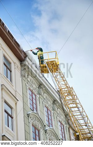 Public Utilities On Special Vehicles Remove Icicles From The Roofs Of Houses On The Rynok Square In