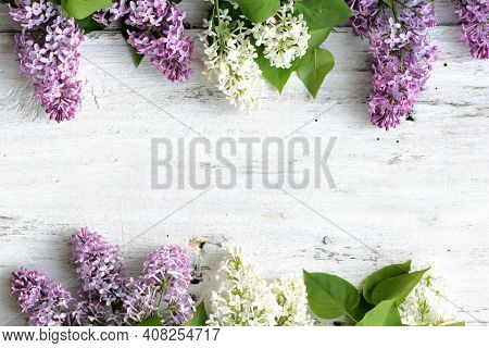 Beautiful Lilac On A Light Wooden Background. Purple And White Flowers Are Arranged Around The Perim