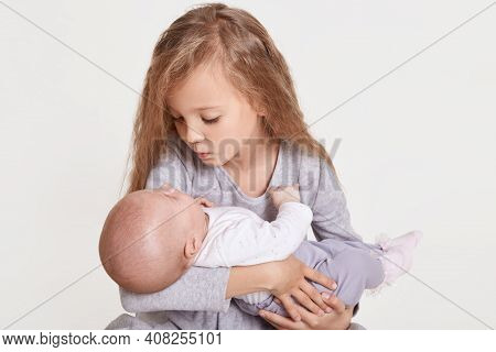 Cute Caucasian Girl Sister Holding Little Baby Indoors. Older Sibling With Younger Sister Newborn. F