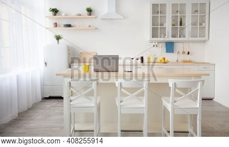 Workspace In Kitchen And Modern Dining Room Interior. Yellow Cup, Laptop And Smartphone On Table, Ch