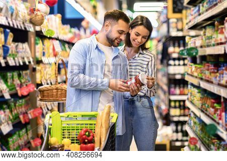 Happy Couple Buying Food In Supermarket, Choosing Products Standing With Trolley Cart Along Aisles A