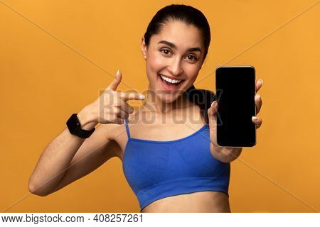 Sports App. Portrait Of Excited Fit Young Lady Holding And Showing Smartphone, Pointing And Indicati