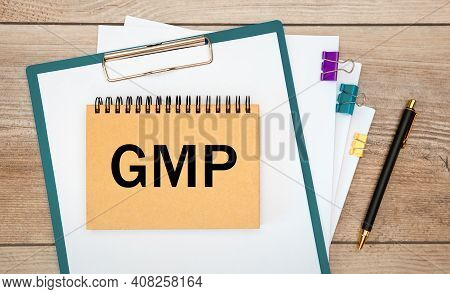 Gmp Good Manufacturing Practice Is Written On A Notepad On An Office Desk With Office Accessories.