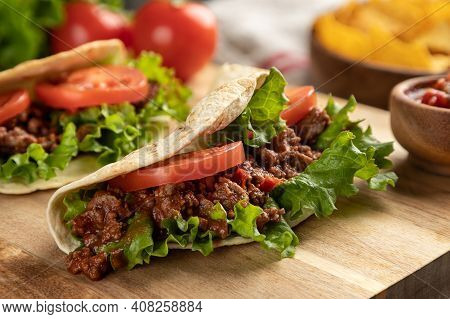 Closeup Of A Beef Taco With Lettuce And Tomato On A Wooden Cutting Board With Tortilla Chips And Sal