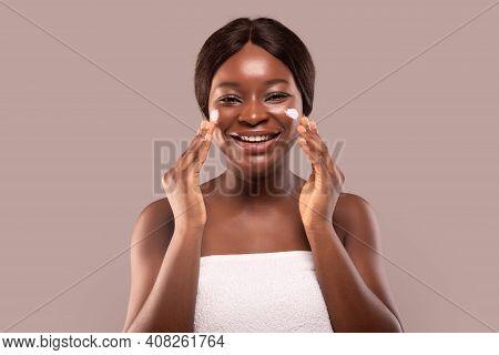Portrait Of Happy Laughing Black Woman Applying Moisturising Anti-aging Cream On Face, Cheerful Afri