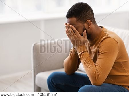 Male Depression. Desperate Depressed African Man Covering Face Crying Having Problems Sitting On Cou