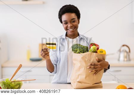 Online Grocery Shopping. Black Lady Showing Credit Card Posing With Groceries Shopper Bag Full Of Ve