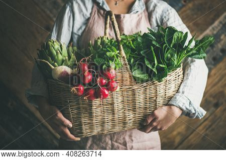 Woman Farmer Holding Basket Of Fresh Organic Garden Vegetables And Greens In Hands, Rustic Wooden Wa