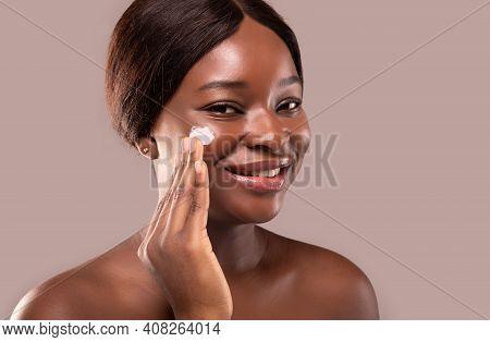 Closeup Portrait Of Beautiful Nude Black Woman Applying Moisturising Cream On Face, Attractive Afric