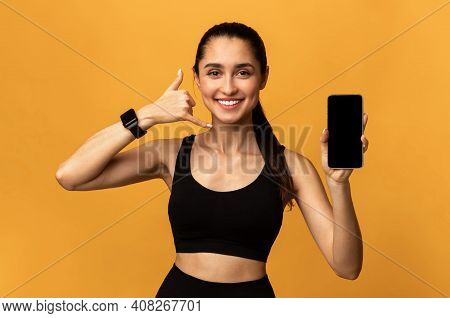 Portrait Of Smiling Fit Young Lady Holding Smartphone With Black Empty Screen For Mockup Template, S