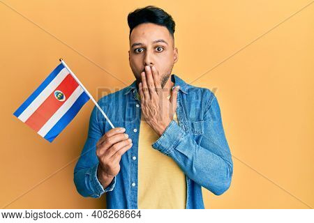 Young arab man holding costa rica flag covering mouth with hand, shocked and afraid for mistake. surprised expression
