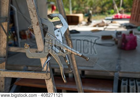 C-clamp Locking Pliers On The Aluminum Folding Stairs In The Construction Site.