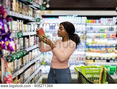 Pretty African American Woman Choosing Groceries At Supermarket, Shopping For Food, Buying Products