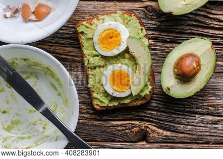 Toast with mashed avocado and eggs on messy rustic wooden table from above