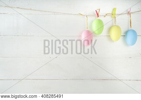 Simple Minimal Easter Greeting Card Background. Colorful Easter Eggs On Craft Cord With Clips Hangin