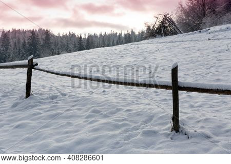 wooden fence on winter meadow in mountains