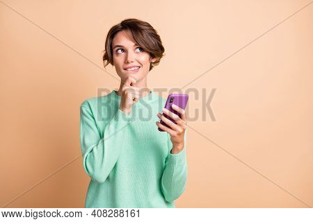 Photo Of Young Woman Curious Dream Dreamy Use Cellphone Look Empty Space Bite Lips Isolated Over Pas