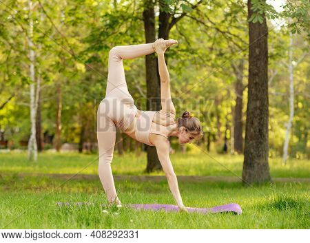 Beautiful Woman Doing Yoga Practice On Park. Spiritual Healing Lifestyle. Caucasian Girl Exercising