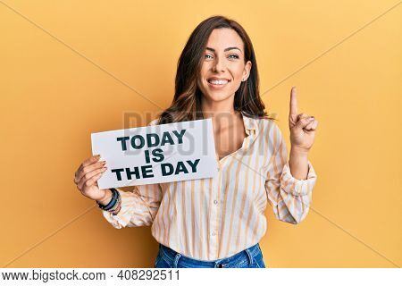 Young brunette woman holding today is the day smiling with an idea or question pointing finger with happy face, number one