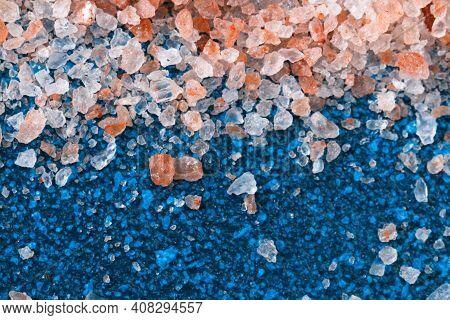 Pink Coarse Salt Crystals On A Blue Table. Himalaya Salt. Background For Advertising Salty.