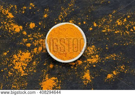 Turmeric Powder On Ardesia Stone Black Background
