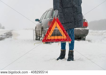Woman Puts Up A Triangle Warning Sign In Close-up On A Road On A Snowy Winter Day. Concept Of Car Br