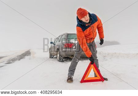 Man In An Orange Jacket Places A Triangle Warning Sign On A Snow-covered Road Against The Background